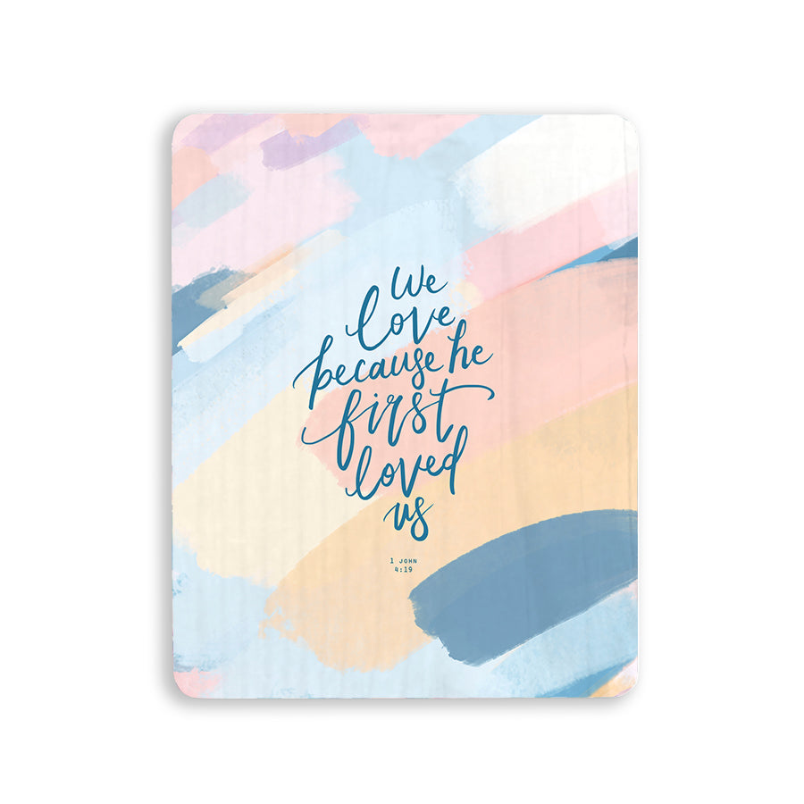 motivational bible verse 'We love because he first loved us' on brush swatches background with blue font details digitally printed on 16cmx20cm quality pine wood.