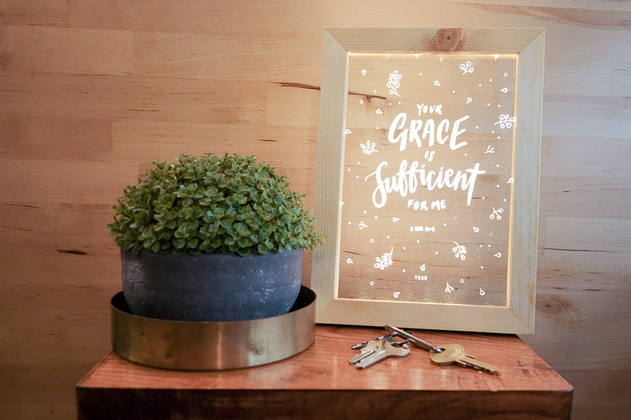 "Night light with wooden frame, acrylic insert, LED energy saving warm white light. 17cmx23cm measurements. leaves details with "" Your grace is sufficient for me "" typography. Placed in front of other night lights on a wooden shelf. Creative Christian living room home decor ideas."
