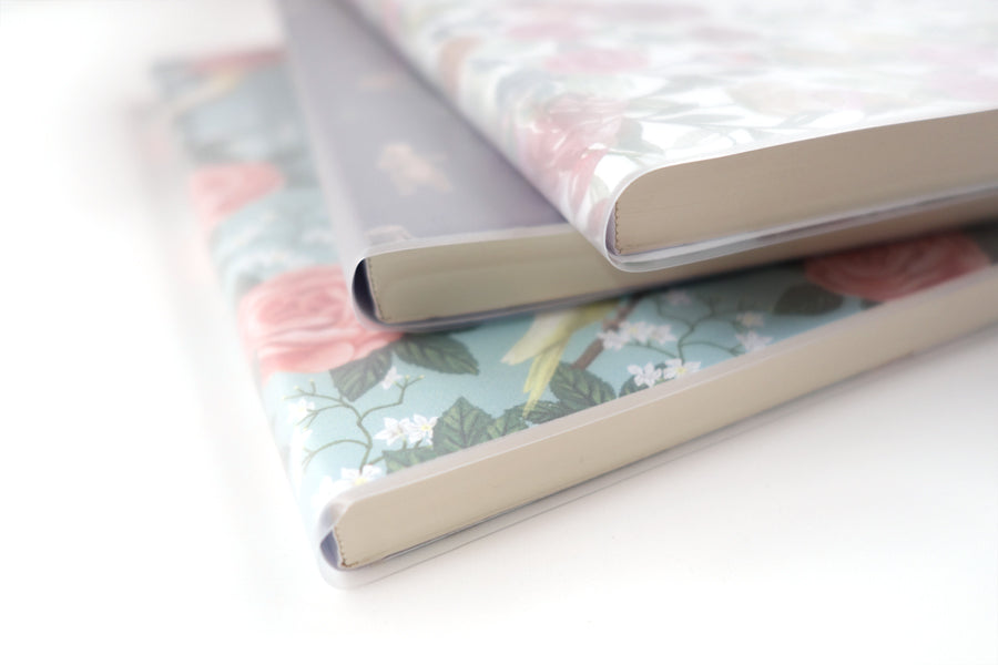 A stack of three noteboooks, with three different themes. 2 garden floral themes and 1 bear themed.