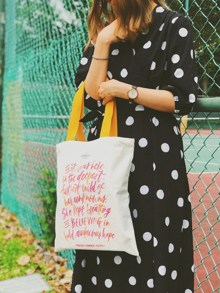 "A lady carries the totebag which carries the message ""believe"""