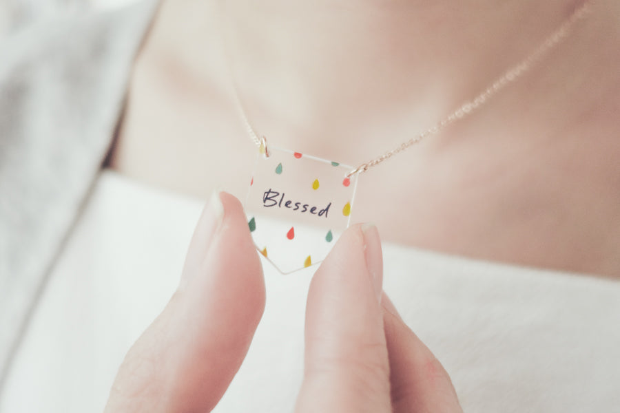 A lady wears Acrylic banner shaped transparent pendant with abstract designs and bible verse 'blessed'. This necklace makes for unique gifts. Rose gold plated stainless steel chains. Pendant height 2.3cm length 2cm. Chain length 42-46.5cm.