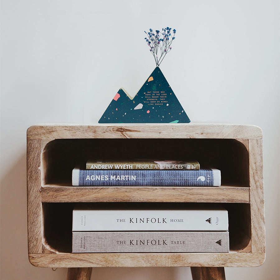 Wooden vase in the shape of a blue wooden mountain vase decorated with dried blue and pink baby's breath. Placed on top of a bookshelf which is stocked with three books.