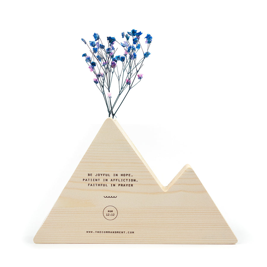 The back of a wooden vase in the shape of a wooden mountains decorated with dried blue and pink baby's breath. The Commandment Co website is at the bottom centre of the vase. Featuring Romans 12:12