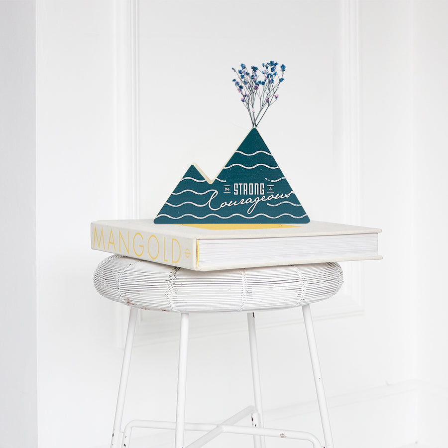 Wooden vase in the shape of a dark mountain. With waves details and white letter typography of bible verse from Joshua 1:9. Decorated with dried blue and pink baby's breath. Placed on a book on a white rattan stool.
