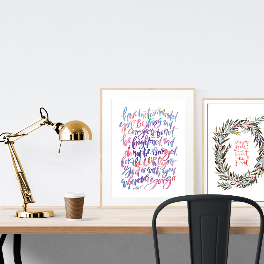 A3 Poster featuring typography of Joshua 1:9 is displayed in a gold frame standing on a wooden table next to a smaller A4 poster with foliage theme.