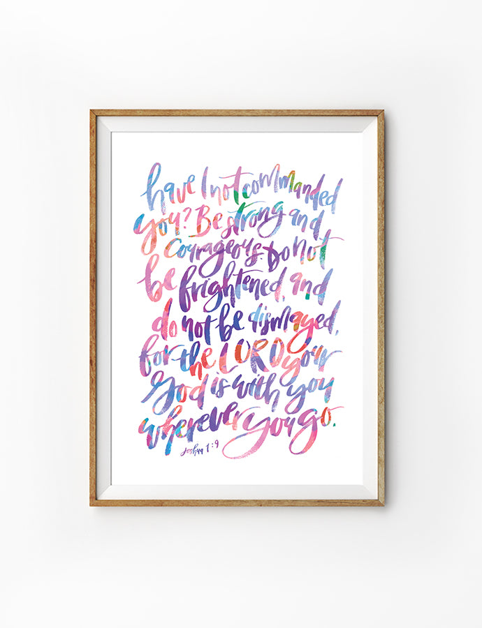Poster featuring neon pastel coloured typography of bible verse from Joshua 1:9 is hung on the wall in a gold photo frame.