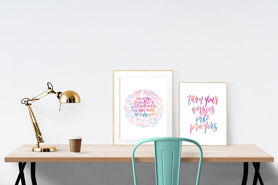 "A3 Poster featuring typography of ""Your love is better than life"" is displayed in a gold frame standing on a wooden table next to a smaller A4 poster with blush pink and white theme."