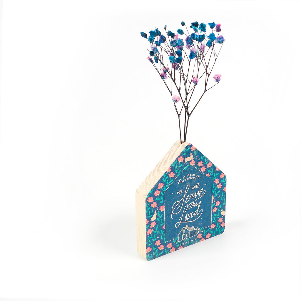 Side view of Wooden vase in the shape of a blue house. With floral details and blue letter typography of 'As for me and my whole family, we will serve the Lord'. Decorated with dried blue and pink baby's breath.