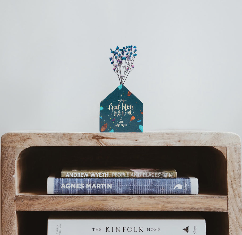 Wooden vase in the shape of a blue wooden house decorated with dried blue and pink baby's breath. Placed on top of a bookshelf which is stocked with three books.