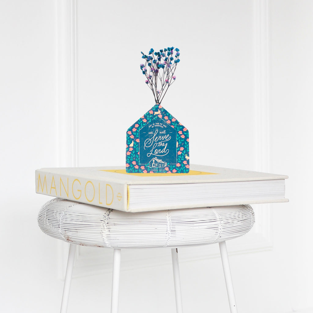 Wooden vase in the shape of a dark blue house decorated with dried blue and pink baby's breath. Placed on a book on a white rattan stool.