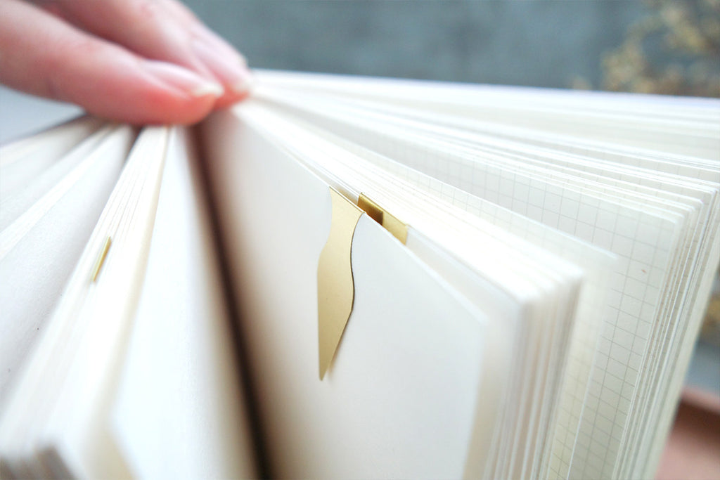 Close up of brass bookmark attaching onto a book