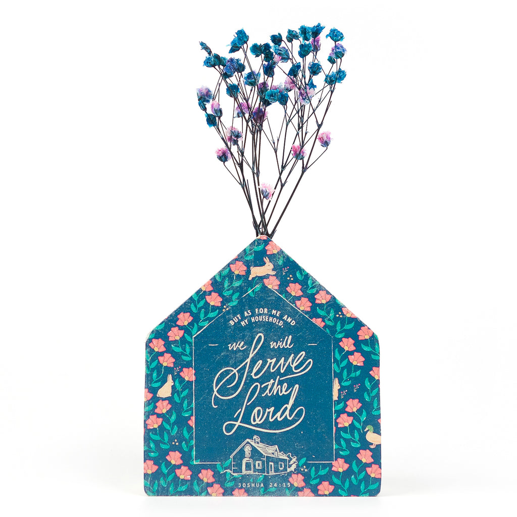 Wooden vase in the shape of a blue house. With floral details and blue letter typography of 'As for me and my whole family, we will serve the Lord'. Decorated with dried blue and pink baby's breath.
