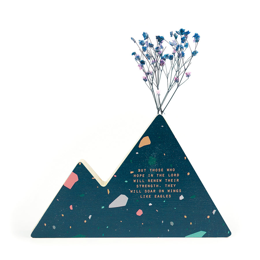 Wooden vase in the shape of a blue mountain. With crosses details and white letter typography of 'But those who hope in the Lord will renew their strength, they will soar on wings like eagles'. Decorated with dried blue and pink baby's breath.