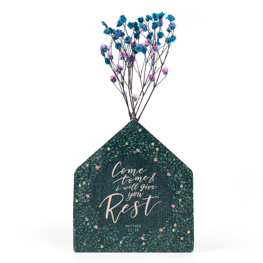 Wooden vase in the shape of a blue house. With crosses details and white letter typography of 'Come to me and I will give you rest'. Decorated with dried blue and pink baby's breath.
