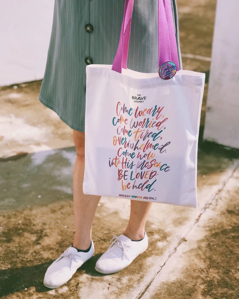 White tote bag with purple straps featuring motivational quote by Morgan Harper Nichols, comes with a colourful pin badge. Measurement: 41cm (H) x 34cm (B) / Strap 28cm