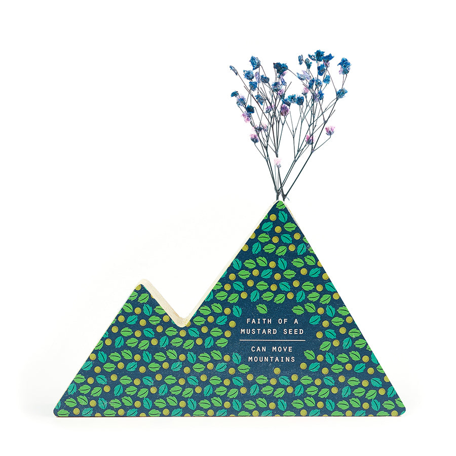 Wooden vase in the shape of a dark mountain. With leaves details and white letter typography of bible verse Faith of a mustard seed can move mountains. Decorated with dried blue and pink baby's breath.