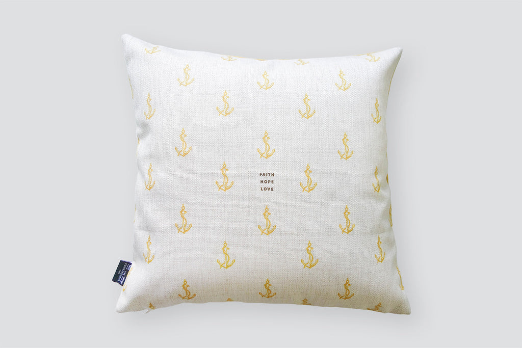 The back of cushion cover features the same design but white with yellow anchor details and brown small fonts. Nautical home design ideas.