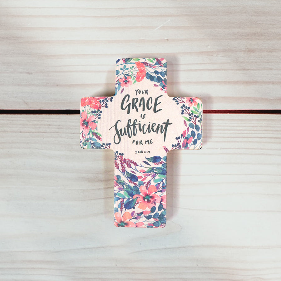 "Wooden cross with flower background and bible verse "" your grace is sufficient"" printed on it."