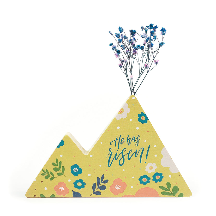 Wooden vase in the shape of a yellow mountain. With floral details and blue letter typography of 'He has risen'. Decorated with dried blue and pink baby's breath.