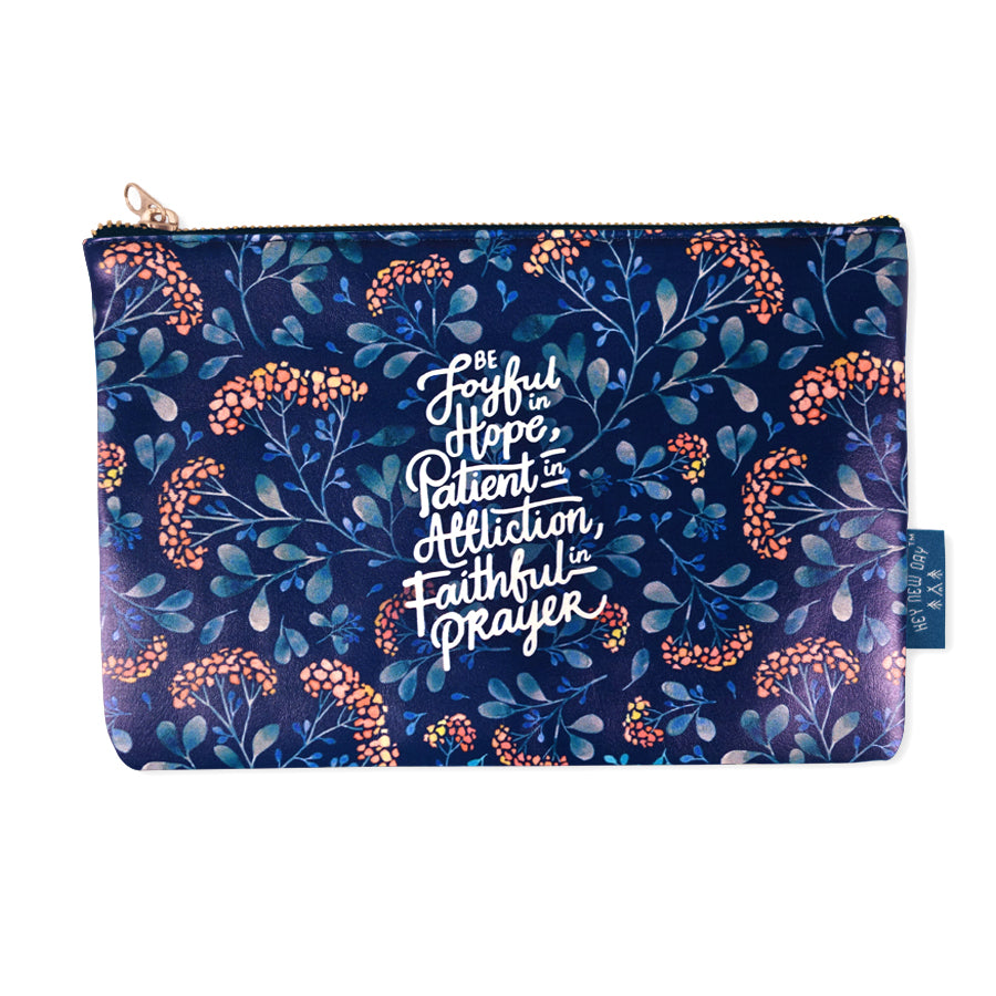 Multipurpose PU Leather pouch in blue painting with garden designs on it. Features bible verse 'Be joyful in hope, patient in affliction, faithful in prayer' in white lettering and is great Christian gift idea. The pouch has inner lining, gold zip. Dimensions: 21cm (W) x 14cm (H)