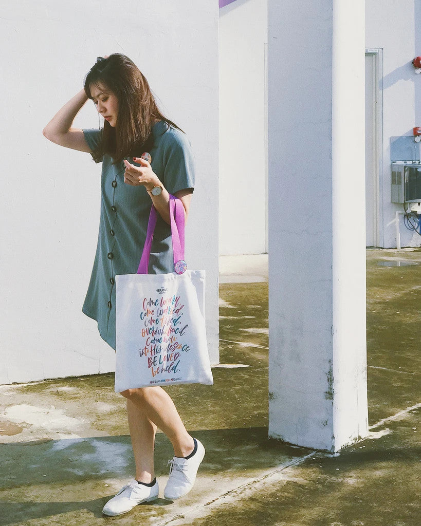 A full body shot of a lady carrying the white tote bag with purple straps and colourful typography of quote by Morgan Harper Nichols. There is a colourful pin badge pinned on the tote bag strap.