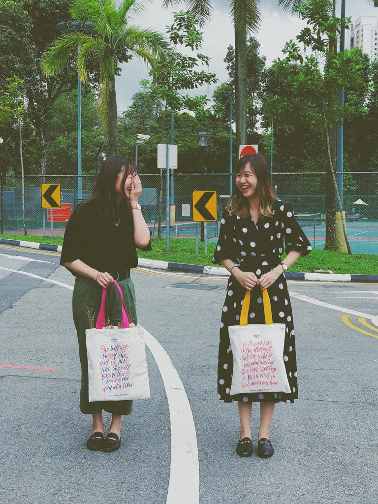 Two ladies carrying the tote bag which carries the message believe