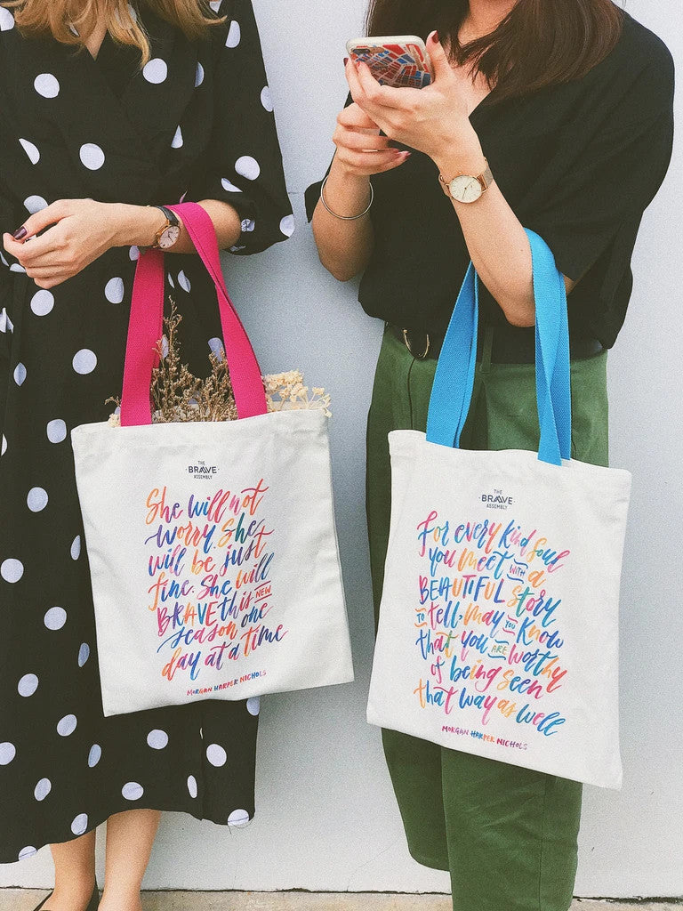 Two girls carrying the collaboration tote bag from the Morgan Harper Nichols collection.