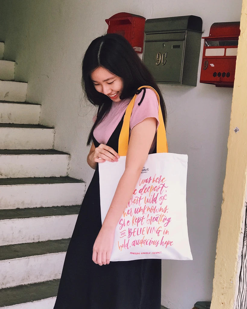 Tote bag made of 100% organic cotton from India. Features a design which carries the message 'believe'. Pink typography on white tote bag.