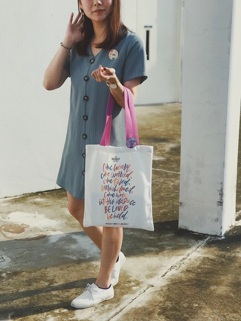 A lady carrying the tote bag with purple straps and colourful typography of quote by Morgan Harper Nichols. There is a colourful pin badge pinned on the tote bag strap.
