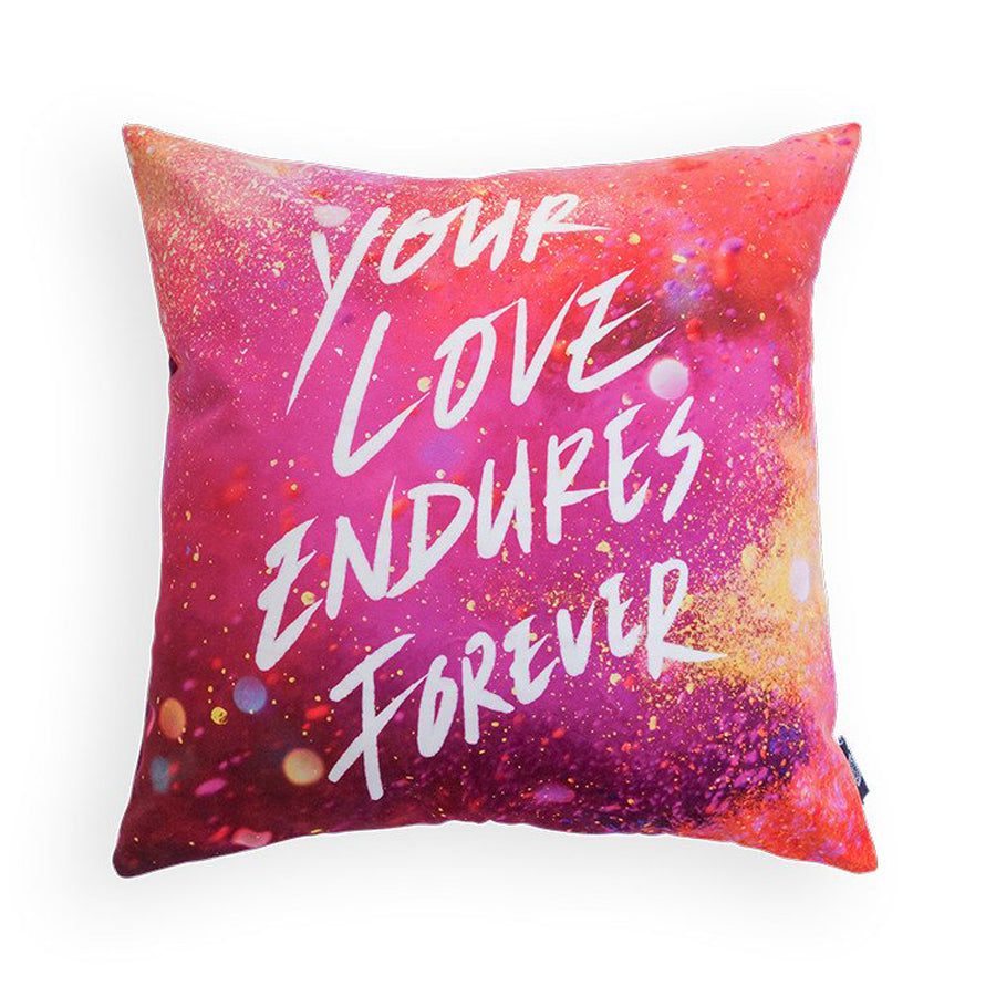 Pillow cover with the verse 'Your love endures forever' in white. On pink glitter and light background