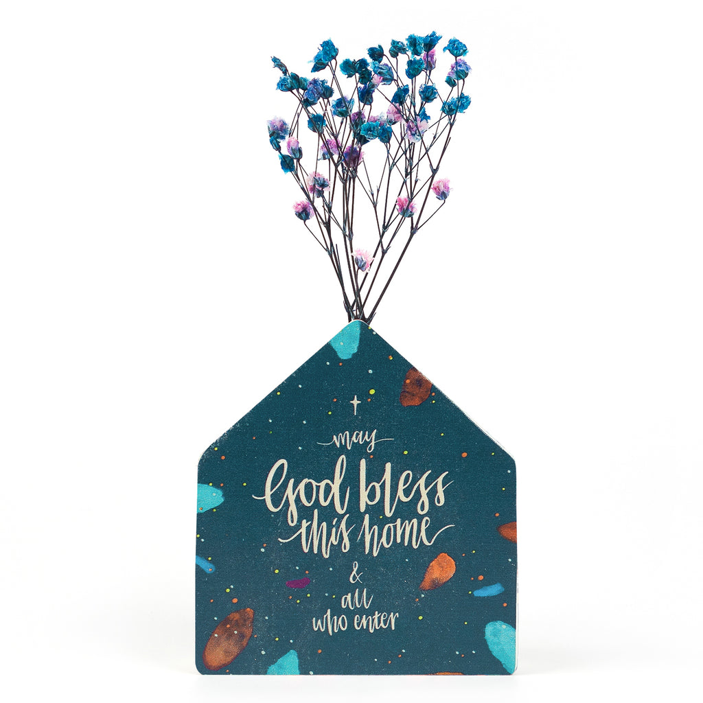 Wooden vase in the shape of a house. With universe details and white letter typography of 'May God bless this home and all who enter'. Decorated with dried blue and pink baby's breath.
