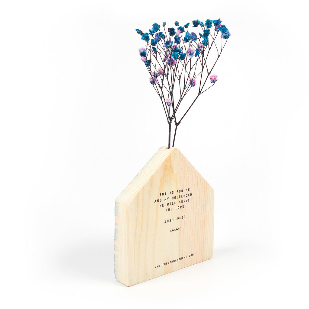 Side view of the back of wooden vase in the shape of a dark blue house decorated with dried blue and pink baby's breath.