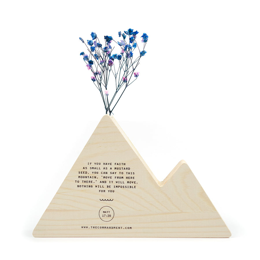 The back of a wooden vase in the shape of a wooden mountain decorated with dried blue and pink baby's breath. The Commandment Co website is at the bottom centre of the vase. Featuring Matt 17:20.