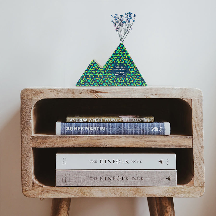 Wooden vase in the shape of a dark blue house decorated with dried blue and pink baby's breath. Placed on top of a bookshelf which is stocked with three books. Great home decor ideas.