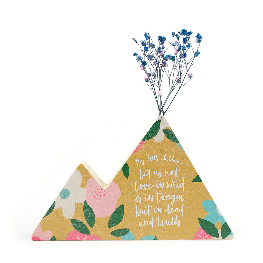 Wooden vase in the shape of a yellow mountain. With floral details and white letter typography of 'Let us not love in tongue but in deed and in truth'. Decorated with dried blue and pink baby's breath.