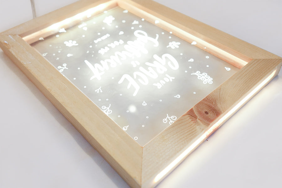 "Close up of night light with wooden frame, acrylic insert, LED energy saving warm white light. 17cmx23cm measurements. leaves details with ""your Grace is sufficient"" typography. A night light hung on the wall."