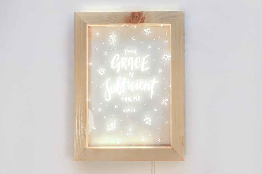 "Night light with wooden frame, acrylic insert, LED energy saving warm white light. 17cmx23cm measurements. leaves details with ""your Grace is sufficient"" typography. A night light hung on the wall."
