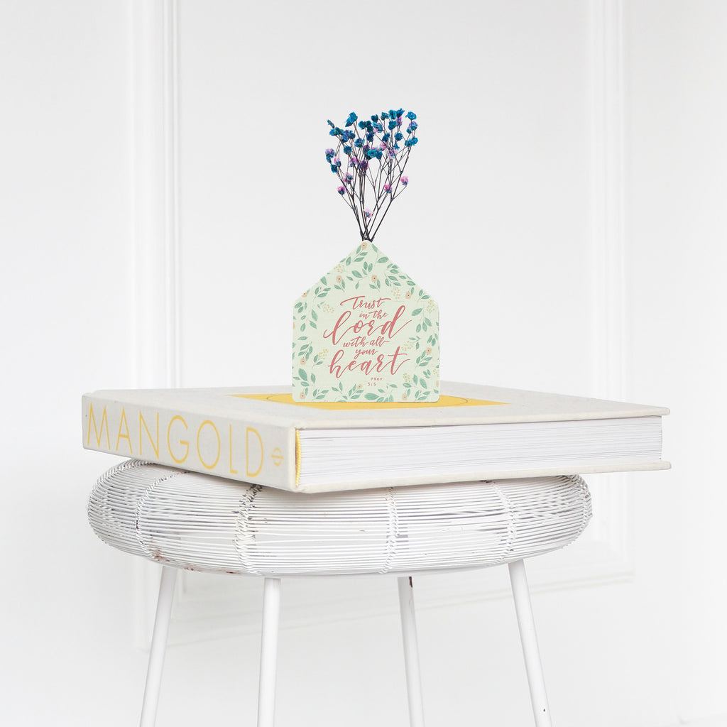 Wooden vase in the shape of a house decorated with dried blue and pink baby's breath. Placed on a book on a white rattan stool.