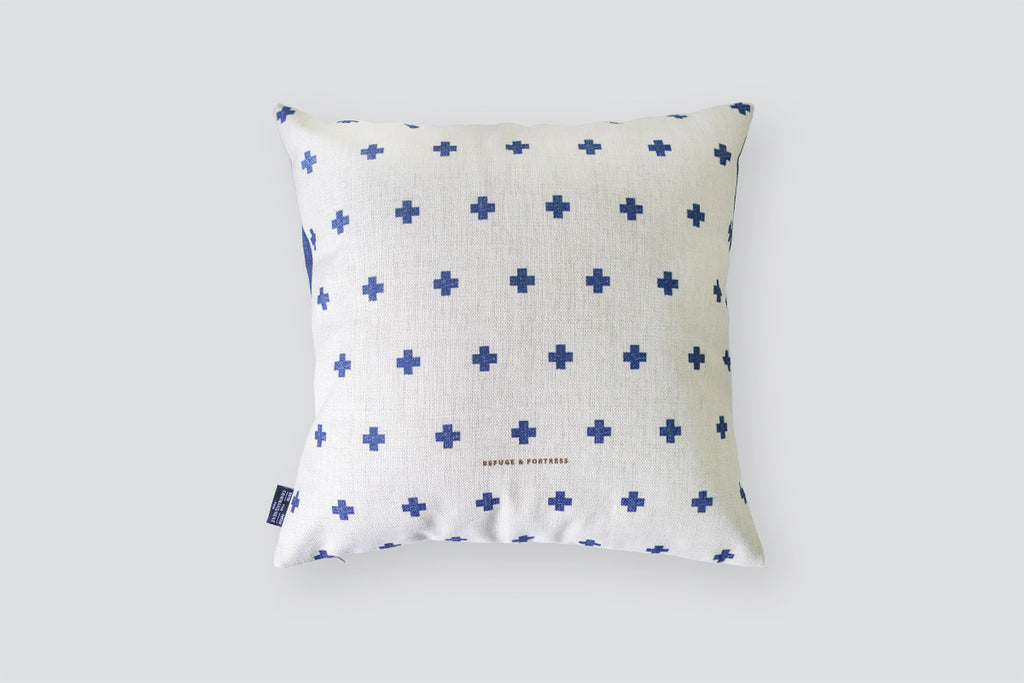 The back of the cushion cover has gray background with blue crosses.