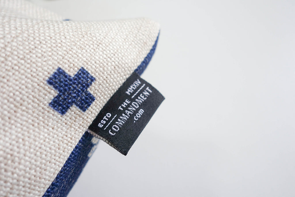 Close up of The Commandment Co back logo which features its website sewn on the pillow cover