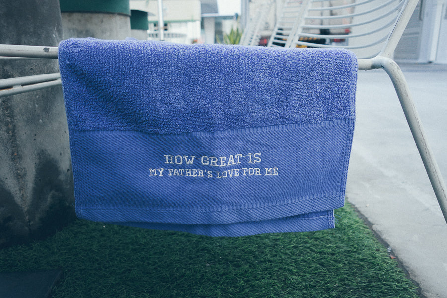 Blue sports towel hanging on handle of chair on top of grass patch