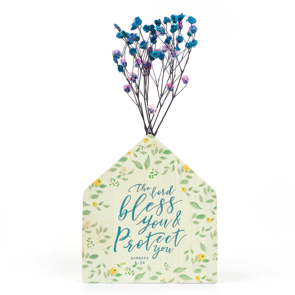 Wooden vase in the shape of a green house. With flowers details and green letter typography of 'The Lord bless you and protect you'. Decorated with dried blue and pink baby's breath.