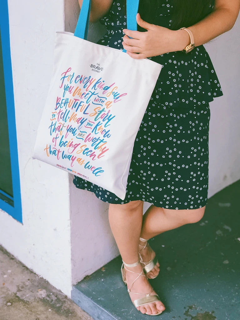 A girl carrying a totebag from the Morgan Harper Nichols collection. Support girls.