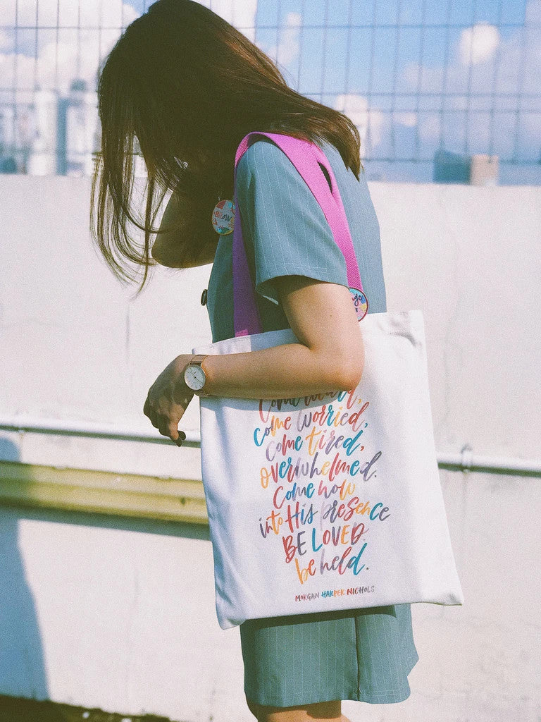 A close up picture of a lady carrying the white tote bag with purple straps and colourful typography of quote by Morgan Harper Nichols. There is a colourful pin badge pinned on the tote bag strap.
