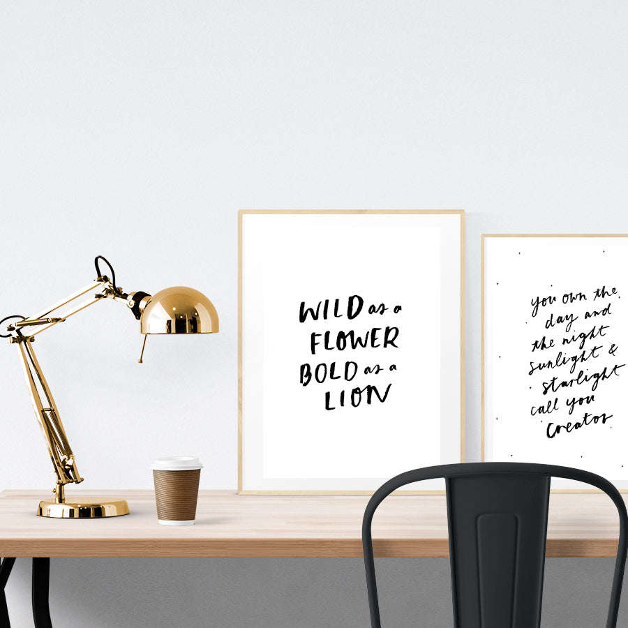 A3 beautiful calligraphy poster placed standing next to a smaller A4 sized calligraphy poster on a wooden table. BnW Christian home interior design ideas.