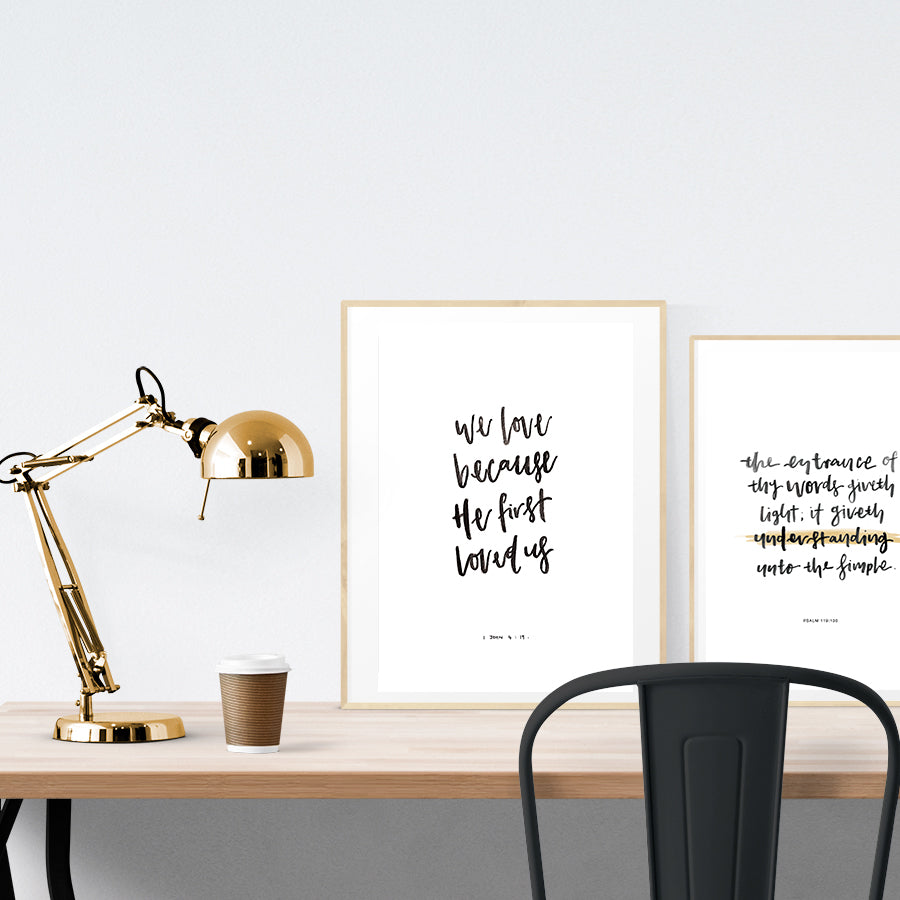 "A3 Poster featuring typography of ""Because we first loved"" is displayed in a gold frame standing on a wooden table next to a smaller A4 poster with typography theme."