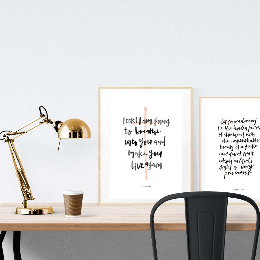 A3 beautiful calligraphy poster placed standing next to a smaller A4 sized calligraphy poster on a wooden table. Modern home interior design ideas. Minimalistic home decor ideas.