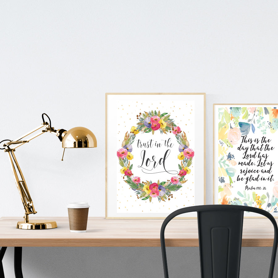 A3 beautiful calligraphy poster placed standing next to a smaller A4 sized calligraphy poster on a wooden table. Pretty Christian home interior design ideas.