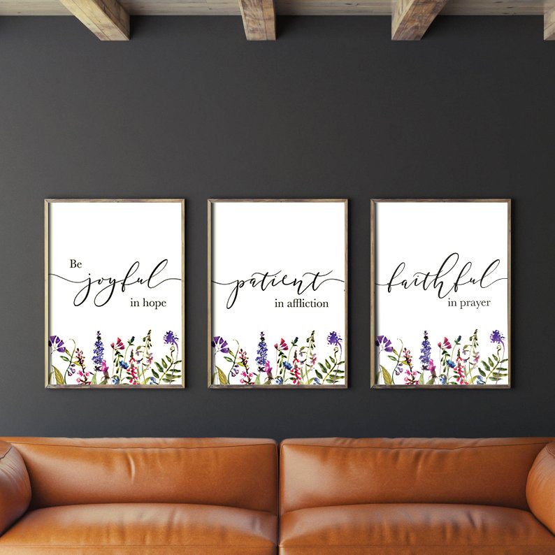 3 Posters featuring beautiful typography bible verses with flower field designs 'Be joyful in hope, patient in affliction, faithful in prayer'. Hung on a black wall, minimalistic rustic home decor ideas.