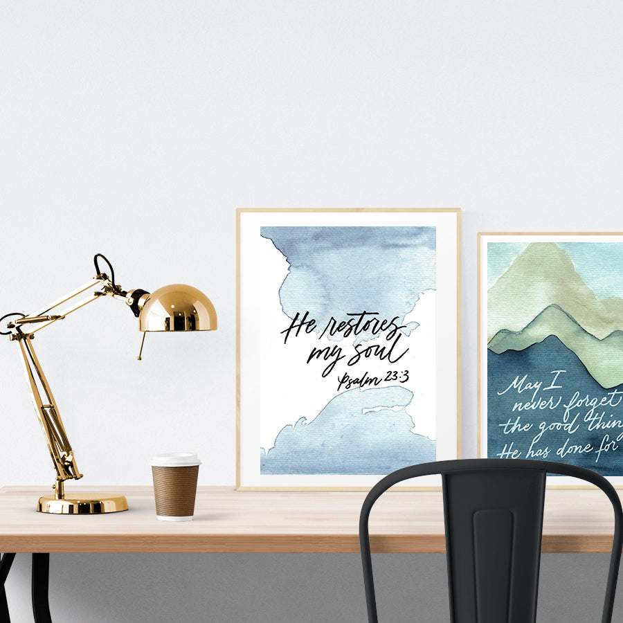 A3 beautiful calligraphy poster placed standing next to a smaller A4 sized mountains painting poster on a wooden table. Inspiring home decor ideas.